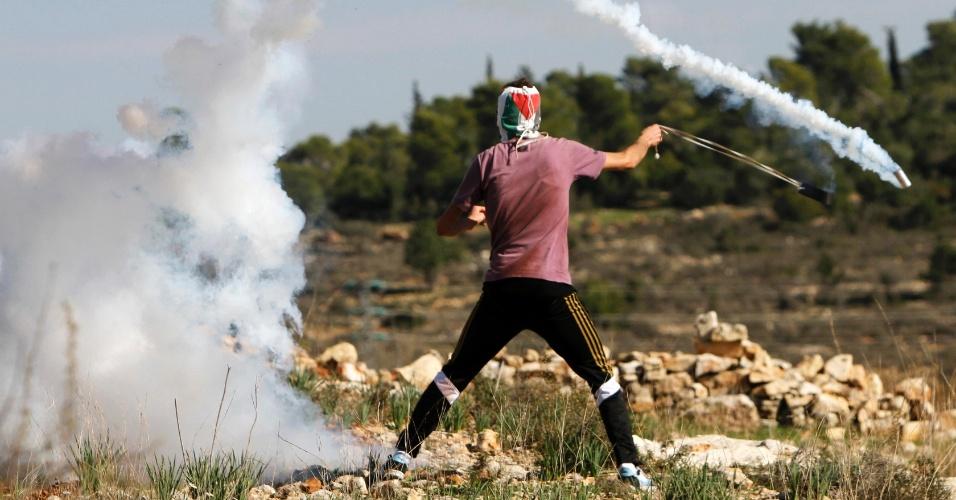 30.nov.2012 - Palestino usa uma funda para devolver granada de gás lacrimogêneo atirada pelo Exército de Israel, nesta sexta-feira (30), na Cisjordânia