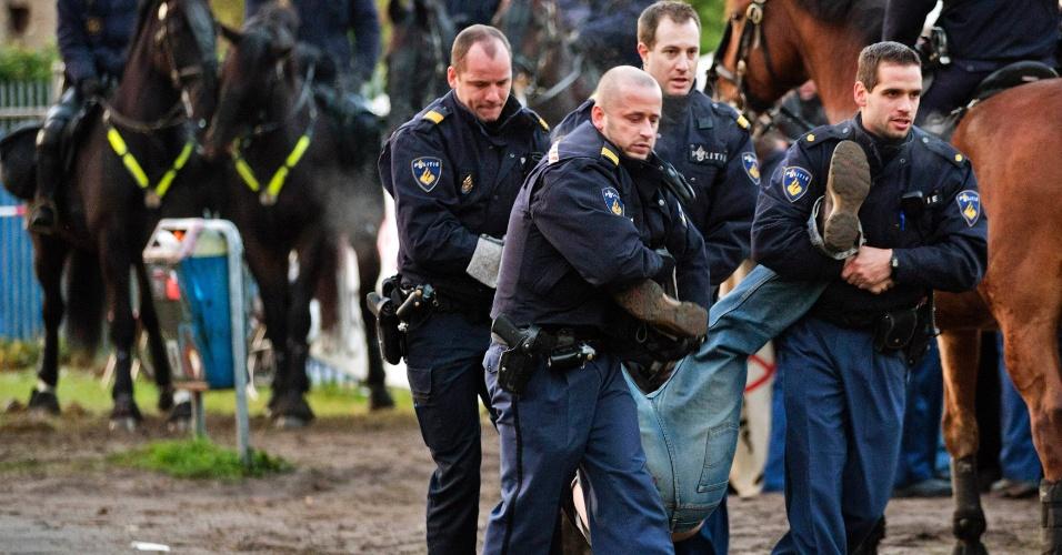30.nov.2012 - Policiais carregam manifestante que bloqueava a entrada de um acampamento montado por imigrantes em busca de asilo, nesta sexta-feira (30), em Amsterdã (Holanda). Um tribunal local rejeitou o pedido de acolhimento feito pelo grupo, e ordenou que eles deixem o local e se preparem para a deportação