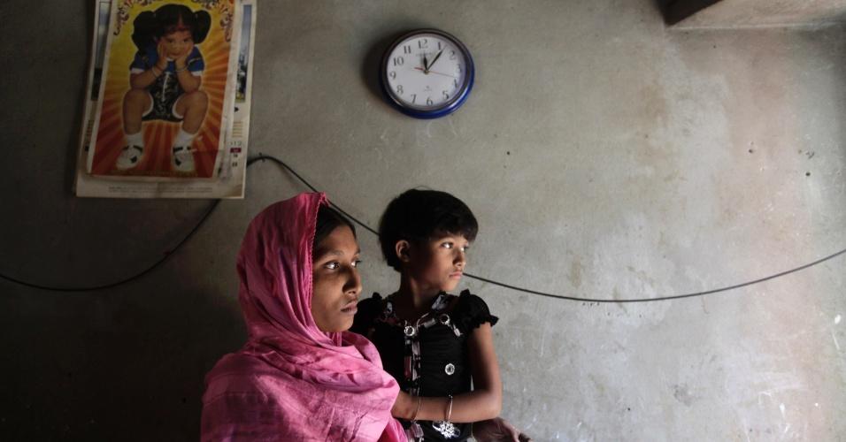 30.nov.2012 - Ruma Akhter, de 23 anos, segura sua filha no colo, nesta sexta-feira (30), em Savar (Bangladesh). Ela sobreviveu ao incêndio em fábrica de roupas, que matou mais de cem trabalhadores no dia 24. Akhter, que ganhava R$ 100 por mês, afirmou que os funcionários raramente faziam exercícios de simulação de incêndio