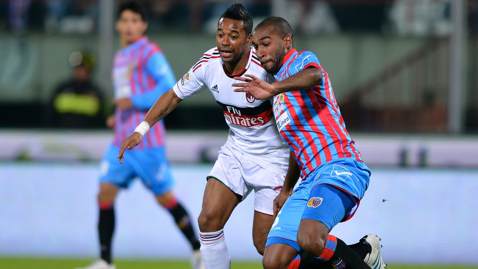 1.dez.2012 - Robinho, do Milan, disputa jogada com Alexis Rolin, do Catania, durante partida do Campeonato Italiano