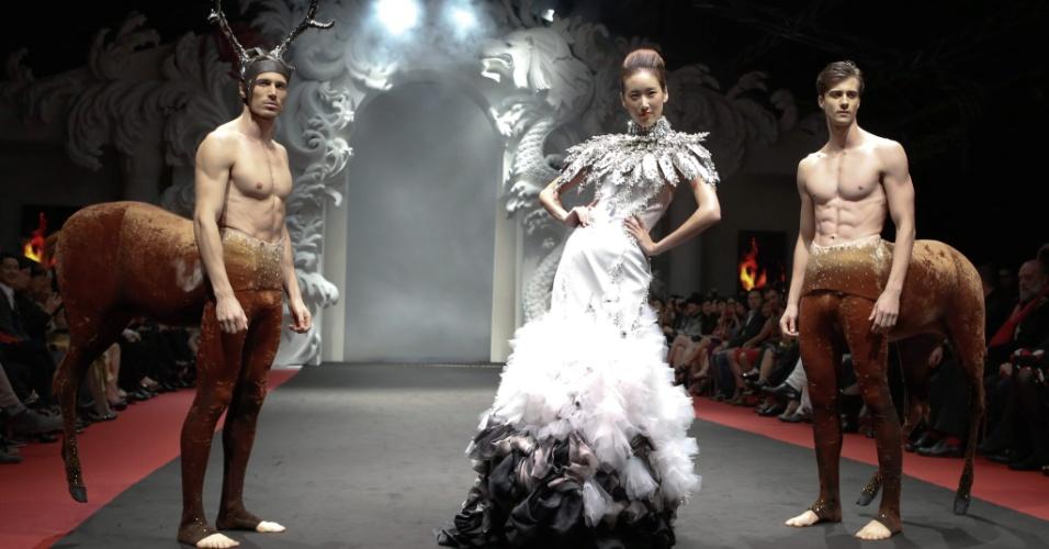 2.dez.2012 - Cercada de rapazes fantasiados de minotauros, modelo apresenta coleção da marca On Aura Tout Vu durante a semana dedicada à moda francesa em Singapura