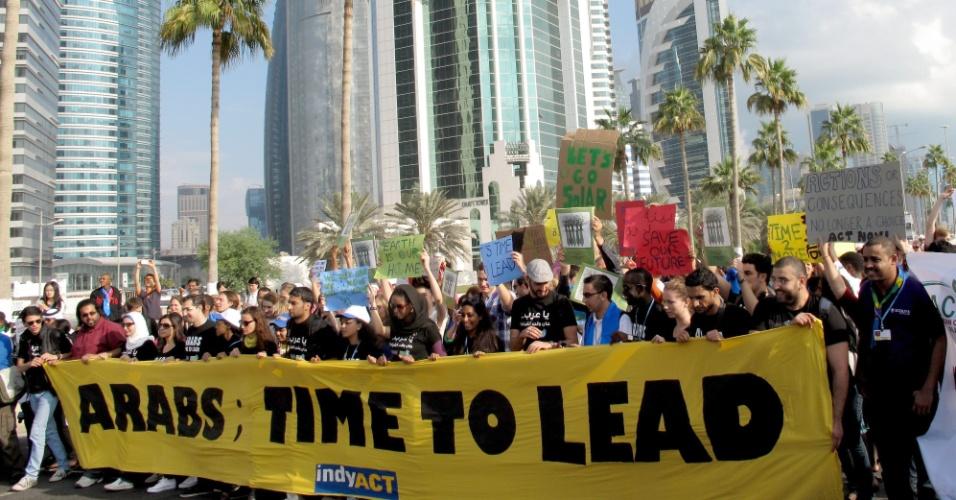 """1.dez.2012 - Jovens árabes exibem faixa com a mensagem """"Árabes, hora de liderar"""", durante manifestação que demanda mais comprometimento com a proteção do clima em Doha, no Qatar, durante a 18º conferência da ONU (Organização das Nações Unidas) sobre as Mudanças do Clima, a COP-18"""