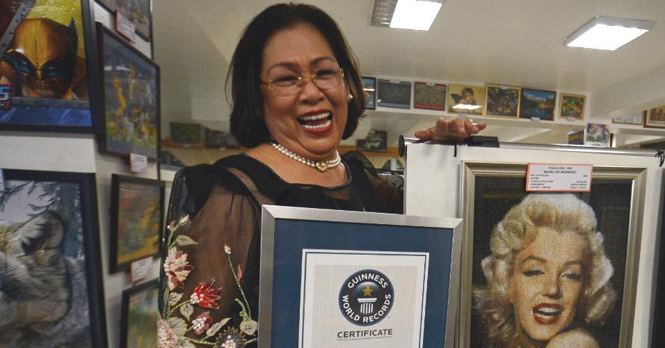 3.dez.2012 - A filipina Georgina Gil-Lacuna segura o certificado do Livro dos Recordes que a reconhece como a maior colecionadora de quebras-cabeça do mundo, perto dos quadros montados com as pecinhas em um ateliê de Tagaytay City, ao sul de Manila (Filipinas). Ela montou mais de mil quebras-cabeça