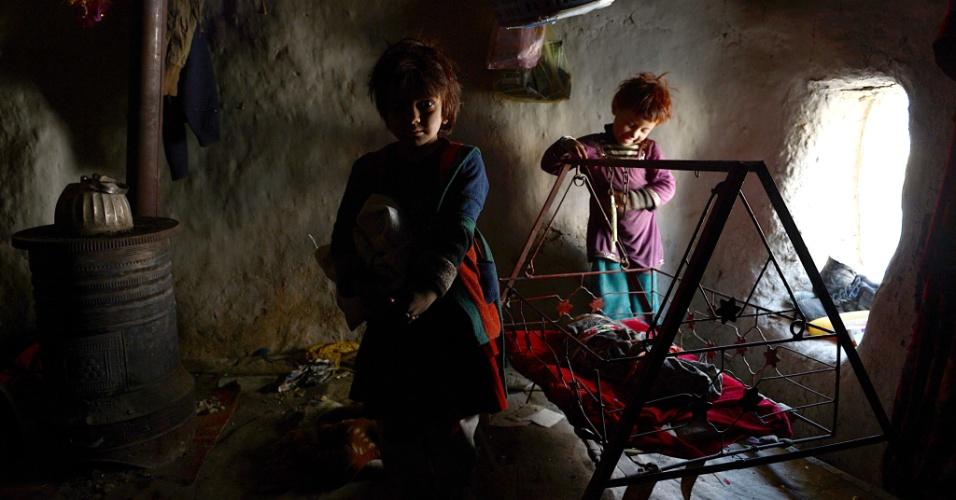 4.dez.2012 - Crianças afegãs desabrigadas brincam dentro de um abrigo de barro em um acampamento improvisado em Cabul. O país tem cerca de meio milhão de pessoas deslocadas e muitos vivem em acampamentos primitivos. Com a chegada do inverno, o tempo frio significa incerteza para alguns
