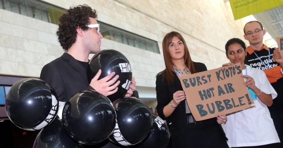 4.dez.2012 - Homem fixa balões de gás em protesto contra o 'hot air', uma espécie de bônus das emissões dos gases de efeito estufa que os países europeus querem usar para diminuir suas metas na segunda fase do Protocolo de Kyoto, que deve ser esboçado pelos ministros de quase 190 países nesta semana.