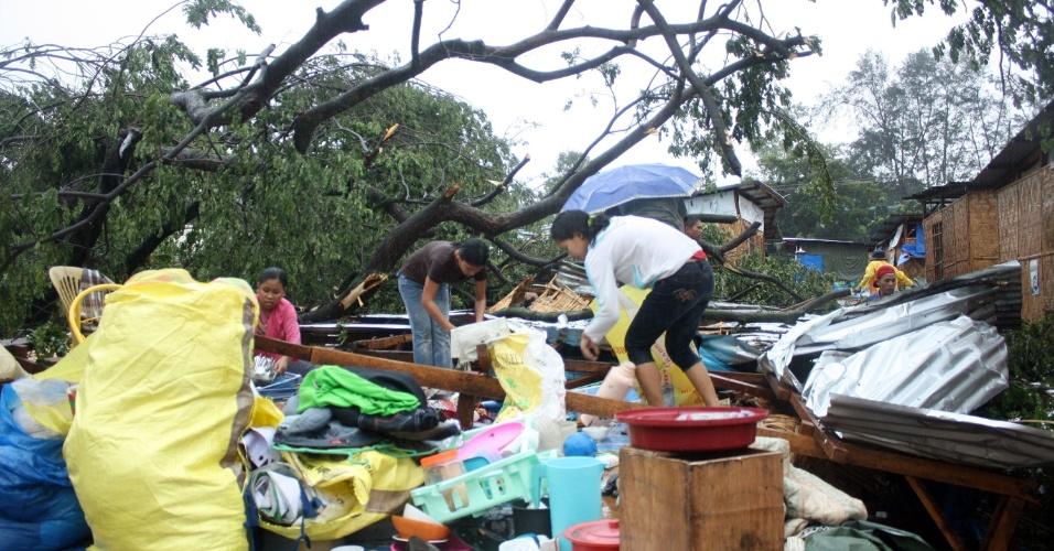 4.dez.2012 - Moradores recolhem pertences depois que sua casa foi destruída pelos fortes ventos do tufão Bopha, que atingiu o sul das Filipinas