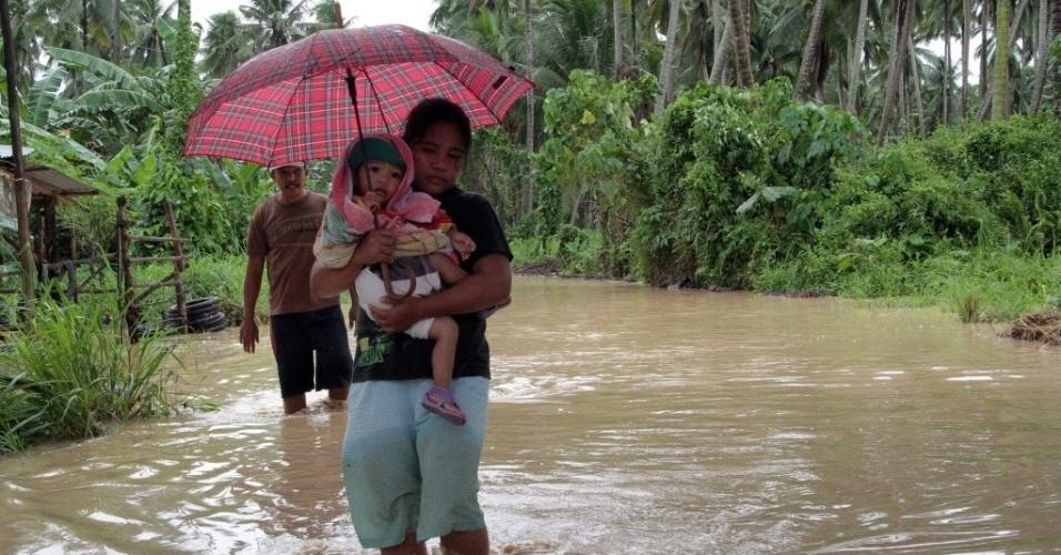 4.dez.2012 - Mulher carrega filho por rua alagada após a passagem do tufão Bopha pelo sul das Filipinas