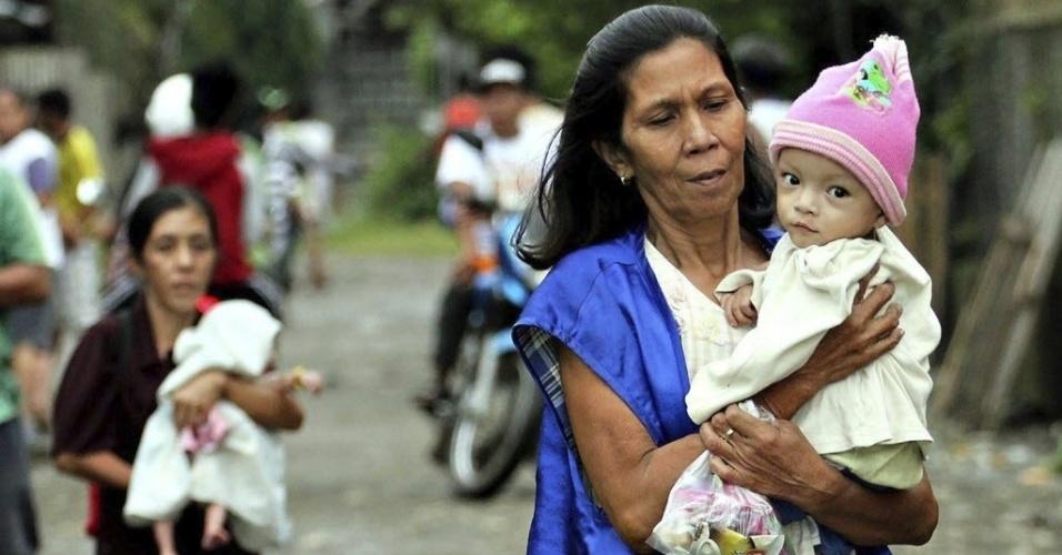 4.dez.2012 - Mulheres levam seus filhos para centro de evacuação após a passagem do tufão Bopha pelo sul das Filipinas