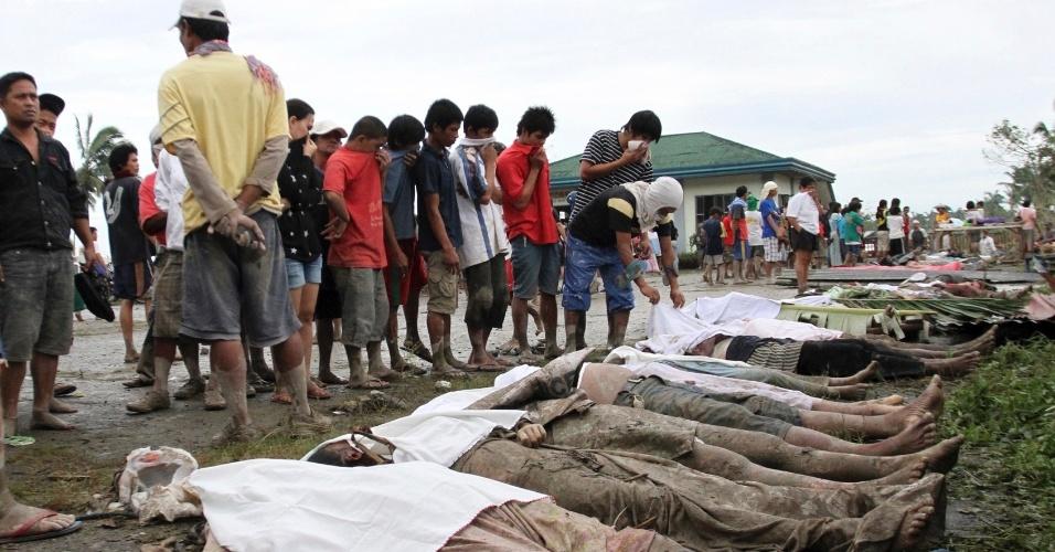 5.dez.2012 - Corpos de pessoas mortas após a passagem do tufão Bopha são enfileirados diante de moradores que buscam por parentes desaparecidos na cidade de New Bataan, no sul das Filipinas