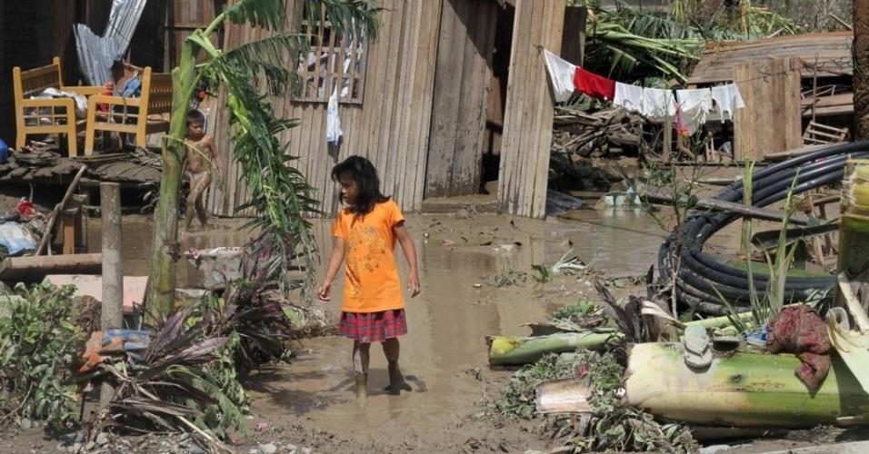 5.dez.2012 - Crianças caminham em frente a casa atingida por enchente após a passagem do tufão Bopha pelo sul das Filipinas