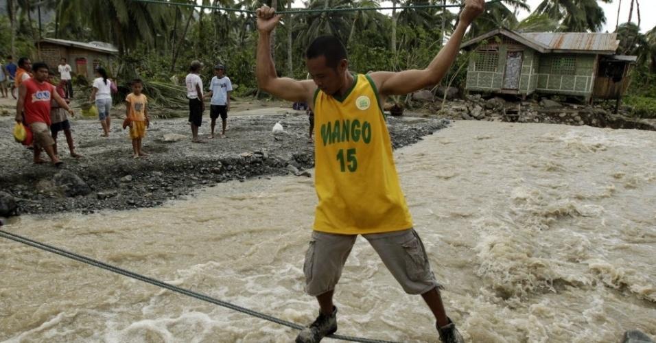 5.dez.2012 - Filipino tenta cruzar se apoiando em cordas estrada que ficou alagada pelas fortes chuvas que caíram no sul das Filipinas após a passagem do tufão Bopha. Dezenas de pessoas morreram e milhares ficaram desabrigados após a passagem do tufão