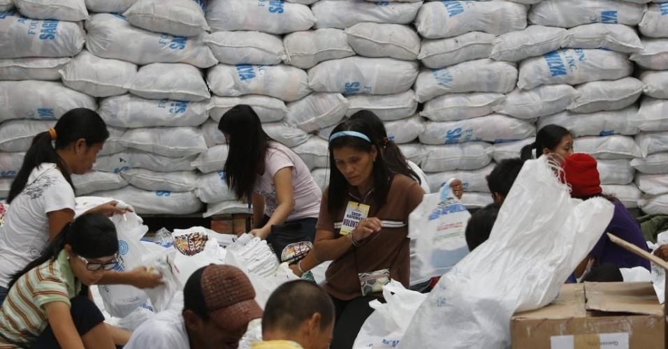 5.dez.2012 - Voluntários filipinos preparam embalagens de ajuda para serem enviadas às regiões das Filipinas que foram atingidas pelo tufão Bopha.