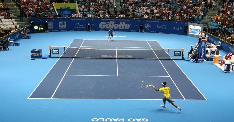 06.dez.2012- Brasileiro Thomaz Bellucci enfrenta o suíço Roger Federer no Desafio Internacional de Tênis no Ginásio do Ibirapuera