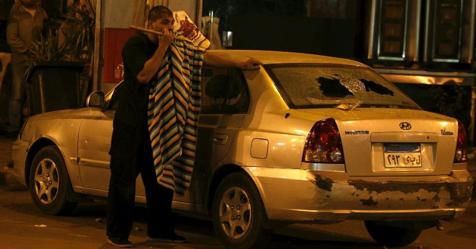 5.dez.2012 - Um apoiador do presidente egípcio, Mohamed Mursi, se protege próximo a um carro atingido durante conflito ocorrido nesta quarta-feira (5) entre manifestantes e muçulmanos, diante do palácio presidencial, no Cairo