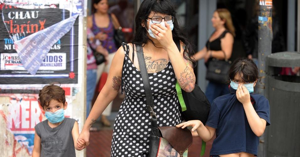 6.dez.2012 - Pessoas caminham usando máscaras como proteção contra uma nuvem com forte cheiro de enxofre que cobria o centro de Buenos Aires, na Argentina