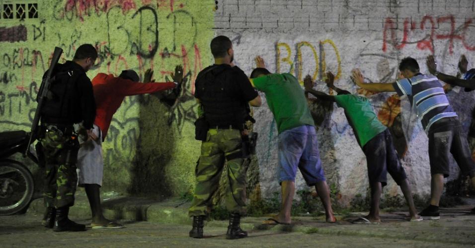 6.dez.2012 - Policiais revistam homens durante operação na comunidade Chico Mendes, em Florianópolis (SC). De acordo com a polícia, a ação é para combater e impedir o tráfico de drogas na localidade