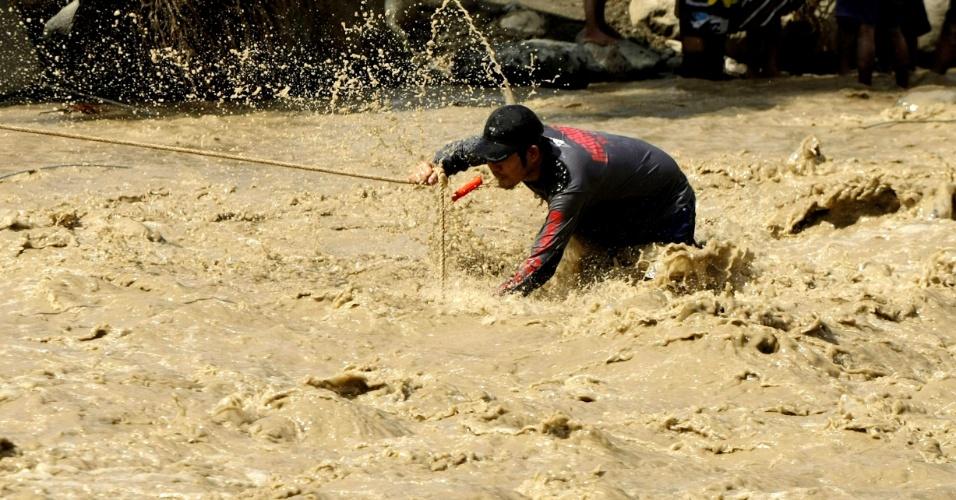 6.dez.2012 - Um membro de equipes de resgate utiliza corda para cruzar correnteza formada nesta quinta-feira (6) por inundação causada pelo tufão Bopha em New Bataan, no sul das Filipinas. As autoridades do país aumentaram para 325 o número de mortos