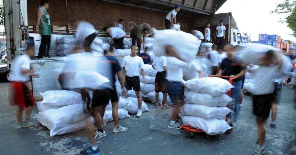 6.dez.2012 - Membros da guarda costeira filipina carregam sacos com suprimentos a serem entregues para as vítimas do tufão Bopha, que atingiu o sul das Filipinas