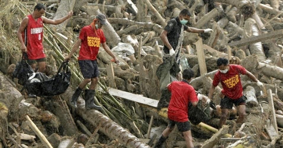 7.dez.2012 - Membros de equipe de resgate  carregam corpos de vítimas do tufão Bopha em meio a troncos de árvores caídos. O tufão atingiu o sul das Filipinas, deixou centenas de mortos e desaparecidos, e milhares de desabrigados