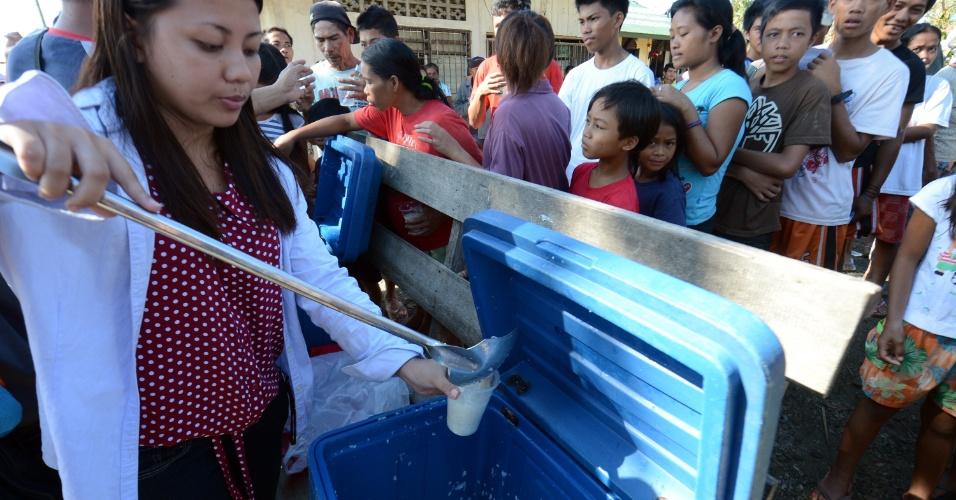 8.dez.2012 - Voluntários de uma igreja distribuem comidas e bebidas aos desabrigados de um povoado no vale Compostela, no sul das Filipinas, após a passagem do tufão Bopha. O número de mortos ultrapassa 500, e outras centenas de pessoas estão desabrigadas