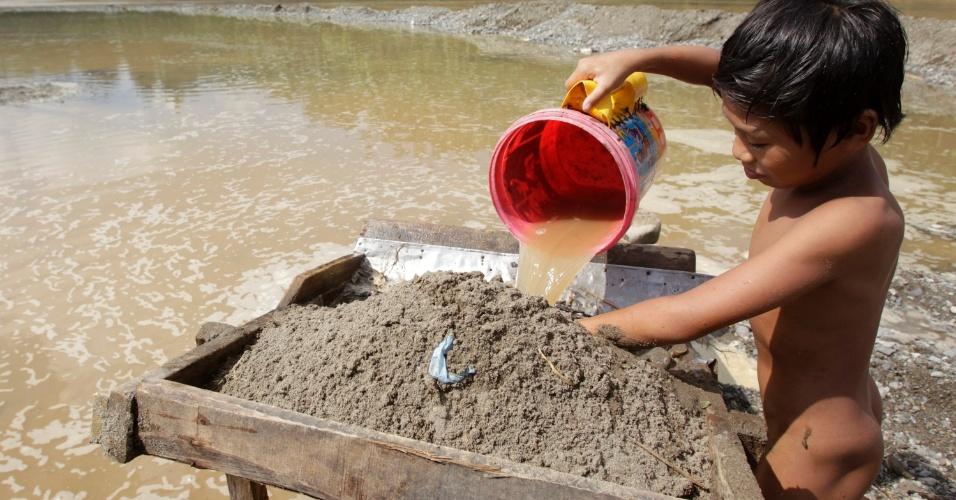 9.dez.2012 - Menino peneira água para usar na lavagem de ouro, em rio em Mawab, no vale Compostela, no sul das Filipinas. A passagem do tufão Bopha varreu a área de mineração causando prejuízo para a população