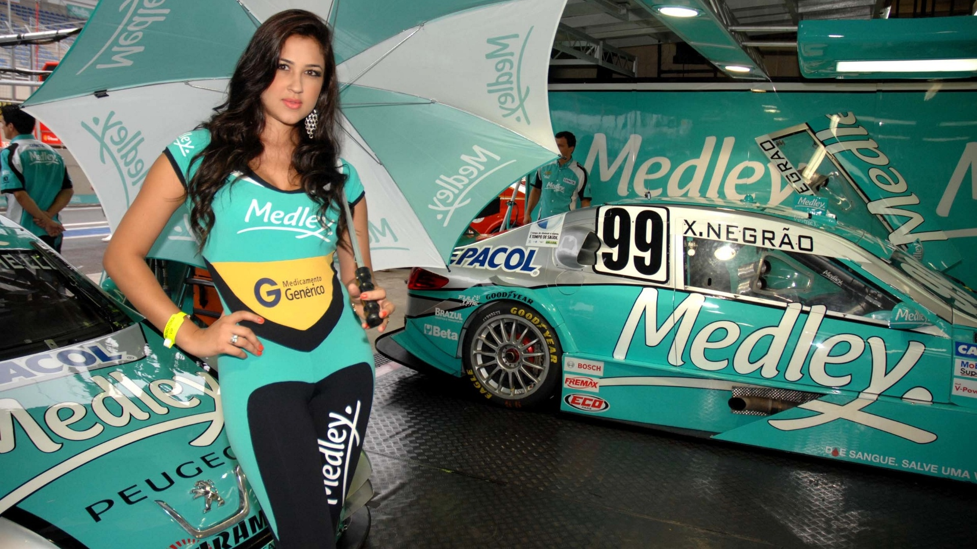 Grid girl posa com guarda chuva na mão no box da Medley