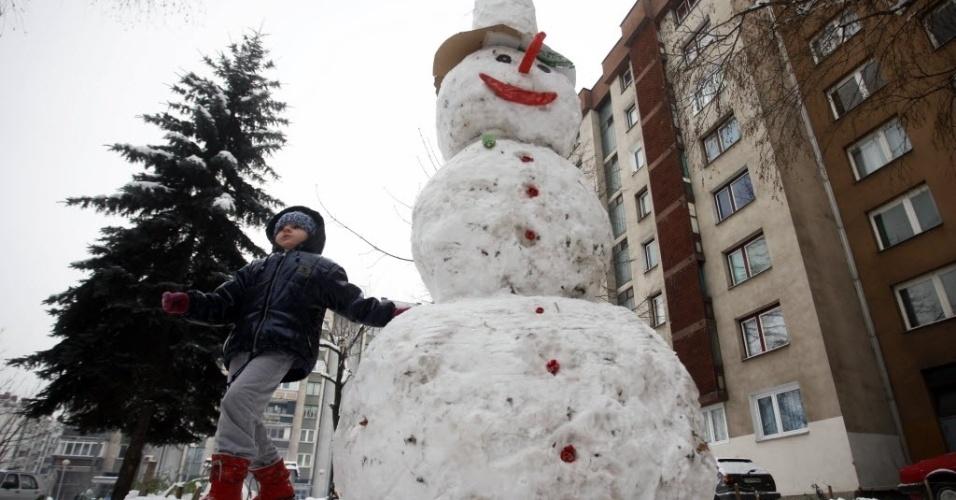 10.dez.2012 - Criança brinca com boneco de neve na cidade de Zenica, na Bósnia-Hezergóvina