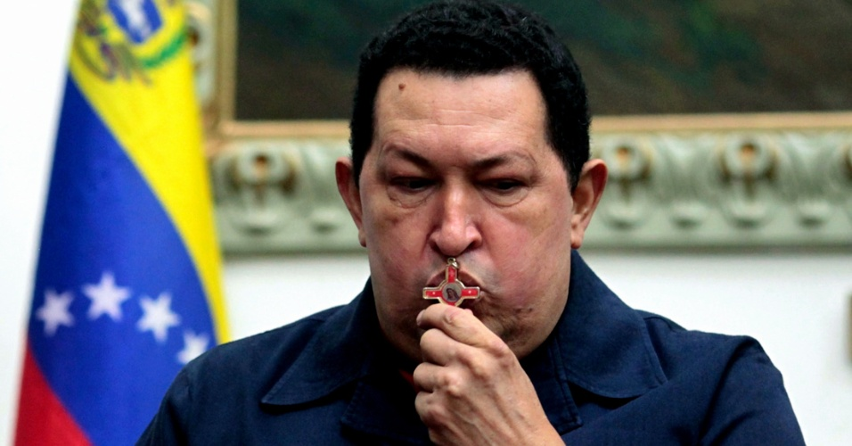10.dez.2012 - Em foto divulgada pela Presidência da Venezuela, o presidente Hugo Chávez beija crucifixo durante reunião com ministros em Caracas, na Venezuela