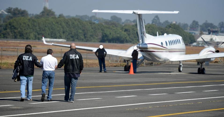 """10.dez.2012 - O guatemalteco Horst Walther Overdick Mejía, conhecido como """"O Tigre"""", é escoltado por policiais americanos, na Guatemala, antes de ser extraditado aos Estados Unidos. Ele foi preso em abril do ano passado a pedido de um tribunal em Nova York, que o acusa de traficar 1,2 tonelada de cocaína da Guatemala para cartel mexicano Los Zetas"""