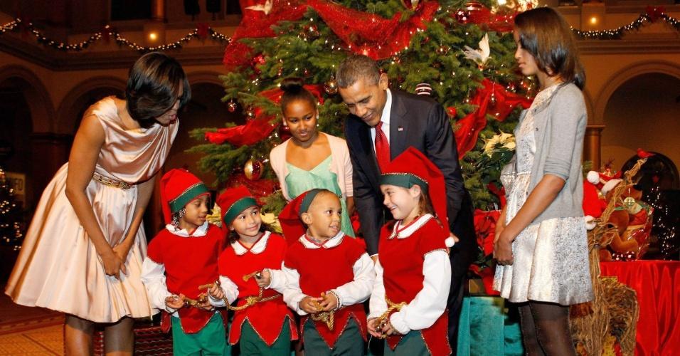 10.dez.2012 - O presidente dos Estados Unidos, Barack Obama, a primeira-dama, Michelle Obama (à esq.), e suas filhas, Malia (à dir.) e Sasha, cumprimentam duendes de Natal, durante o evento Natal em Washington, na capital americana