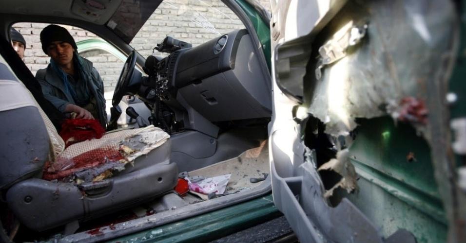 10.dez.2012 - Policial afegão inspeciona veículo blindado usado por uma autoridade policial que morreu após uma explosão de bomba ter atingido o veículo, em Herat, no Afeganistão
