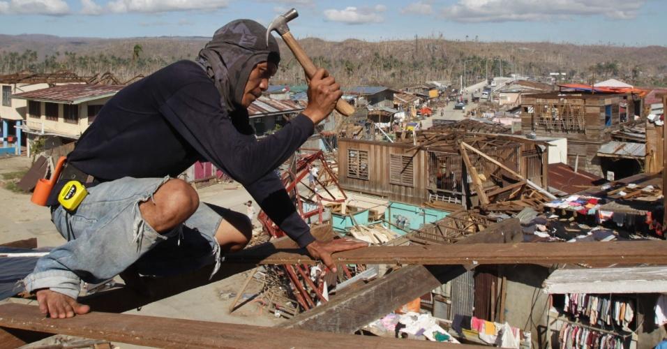 11.dez.2012 - Homem tenta reconstruir sua casa, que ficou completamente destruída após a passagem do tufão Bopha pela cidade de Baganga