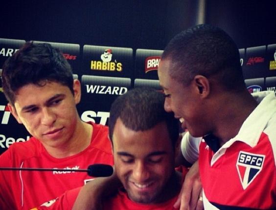 11.dez.2012 - Lucas é abraçado por Wellington e Oswaldo em sua última entrevista coletiva no CT do São Paulo antes de se mudar para a França, onde defenderá o PSG