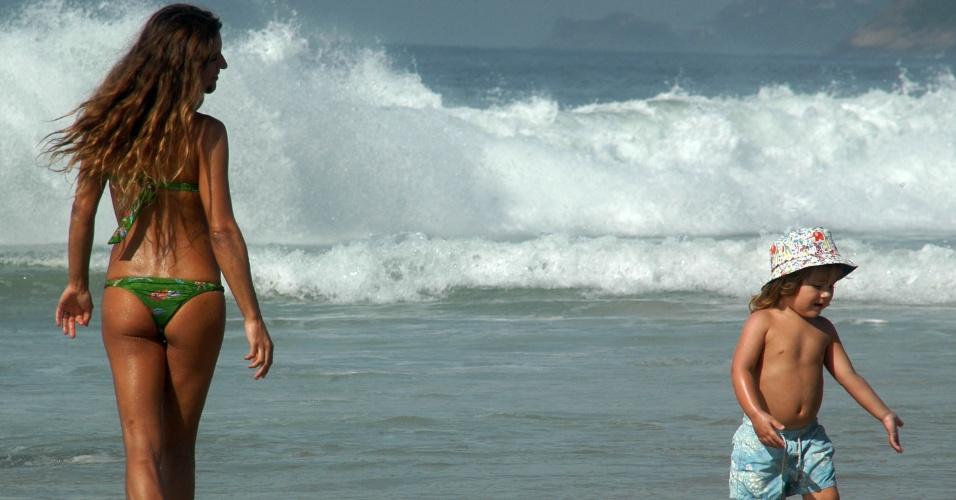 11.dez.2012 - Mulher e criança se aproximam do mar na praia de Ipanema, no Rio de Janeiro, nesta terça-feira