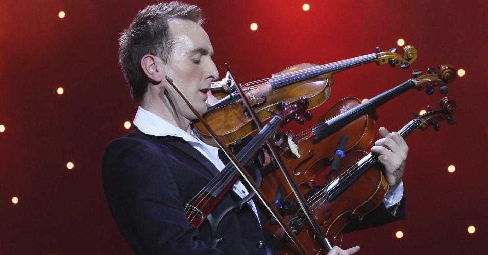 11.dez.2012 - O violinista ucraniano Oleksandr Bozhyk toca quatro violinos ao mesmo tempo durante tentativa de bater um recorde mundial na cidade de Lviv, na Ucrânia