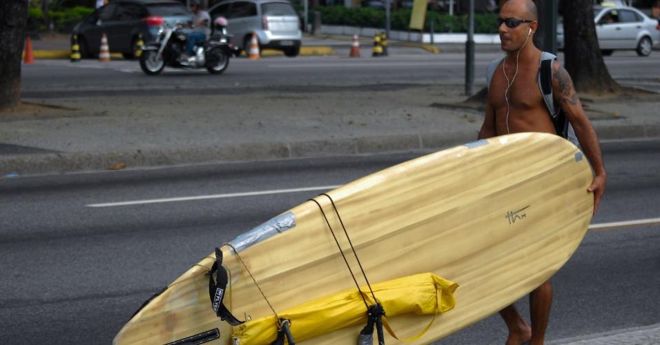 11.dez.2012 - Surfista carrega prancha com rodinhas na praia de Copacabana, no Rio de Janeiro, nesta terça-feira