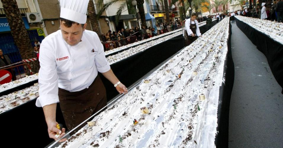 11.dez.2012 - Um dos confeiteiros mede uma sobremesa de Natal feita em Aspe, na província espanhola de Alicante, que se tornou a mais comprida do mundo com 1.174,28 metros
