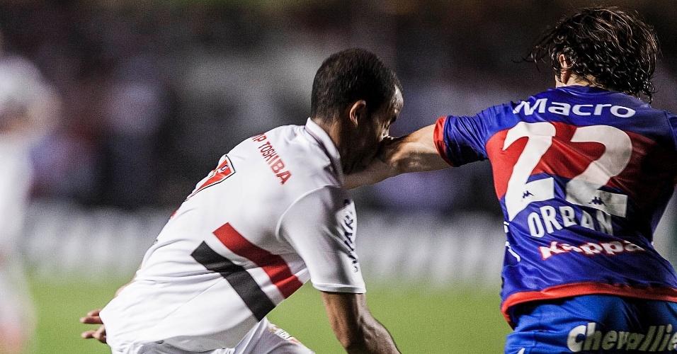 12.dez.2012 - Jogador Orban, do Tigre, atinge Lucas, do São Paulo, com o cotovelo