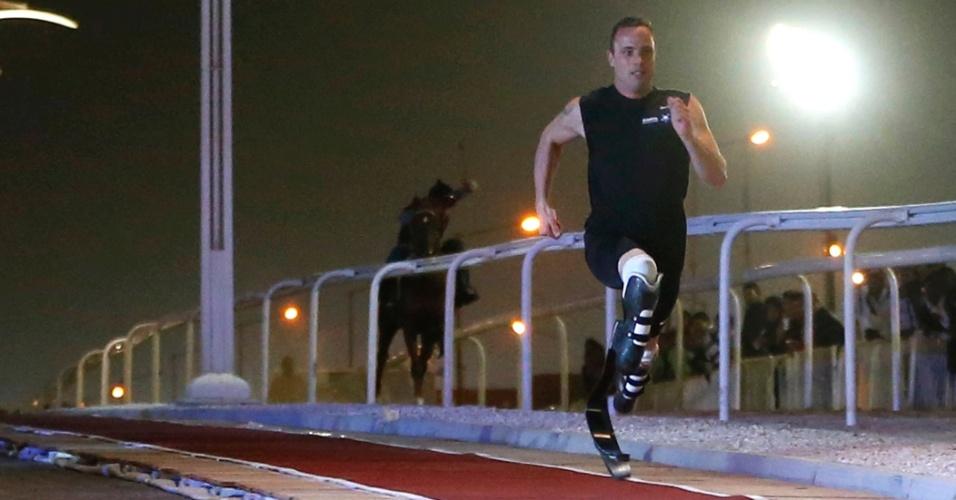 12.dez.2012 - Oscar Pistorius vence corrida de exibição contra cavalo puro-sangue no Qatar