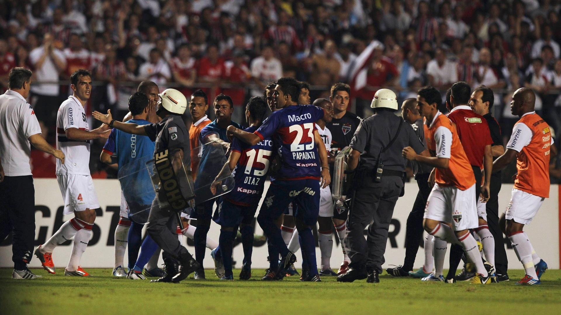 12.dez.2012 - Policiais entram em campo para separar confusão entre jogadores do São Paulo e do Tigre