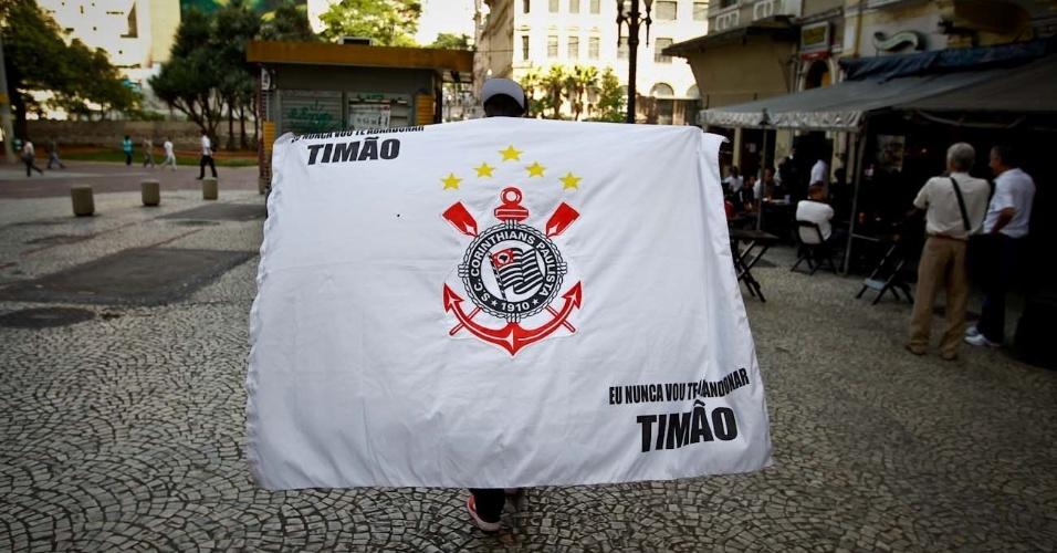 12.dez.2012 - Torcedor caminha com bandeira do Corinthians nas costas pelo centro de São Paulo