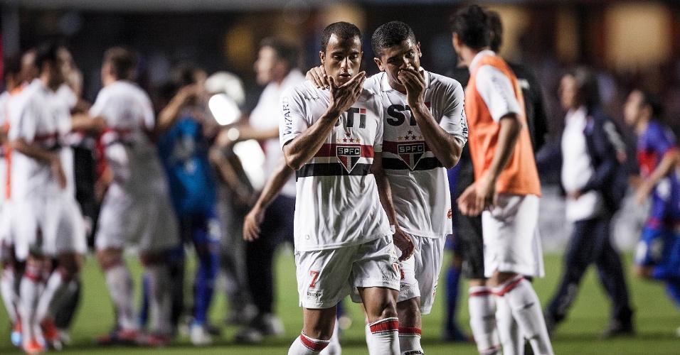 12.dez.2012 - Lucas deixa o campo ao fim do primeiro tempo; ao fundo, jogadores de São Paulo e Tigre se envolvem em confusão