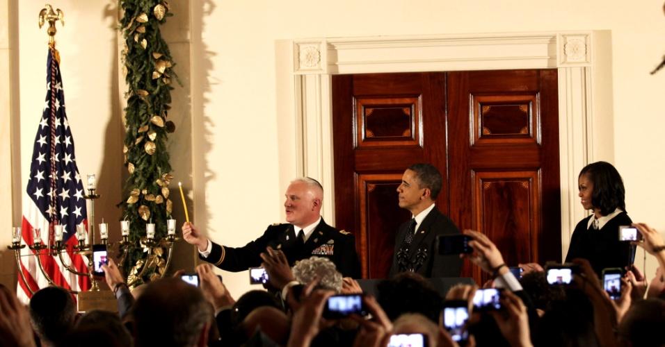 13.dez.2012 - O rabino Larry Bazer acende a Menorá no Grande Salão da Casa Branca, enquanto é observado pelo presidente norte-americano, Barack Obama, e a primeira-dama, Michelle Obama, em celebração do Chanuká