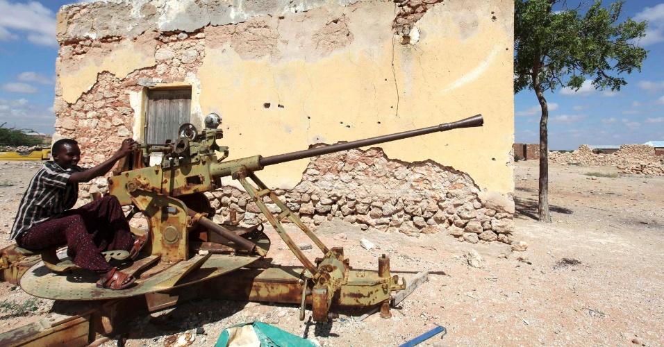14.dez.2012 - Homem mexe em uma metralhadora anti-aérea abandonada em Dhusamareeb, na Somália, área dominada por muçulmanos sufistas