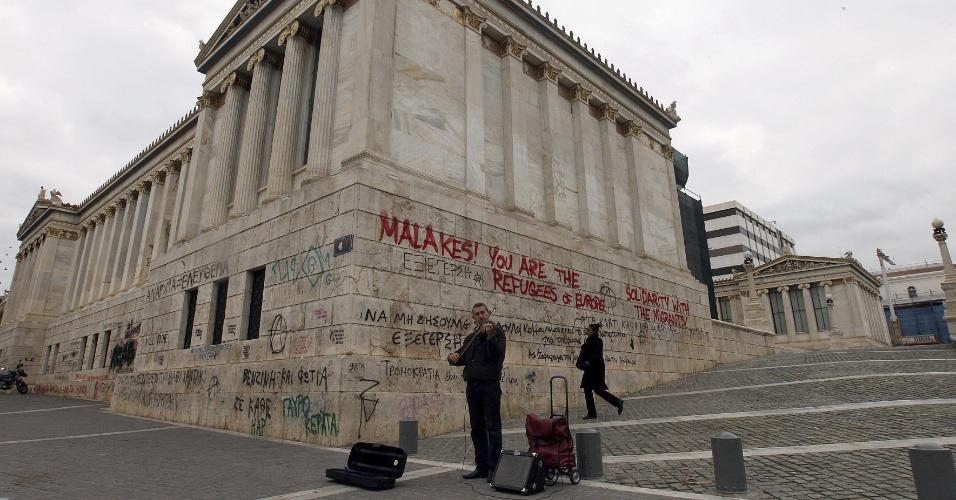 14.dez.2012 - Homem toca violino em rua de Atenas nesta sexta-feira (14). A taxa de desemprego no país chegou a 24,8% no terceiro trimestre deste ano, índice 7,1% superior ao mesmo período do ano passado. O número equivale a 1,2 milhão de desempregados no país, informou o governo grego. O desemprego é ainda pior entre os jovens com 15 e 24 anos e mulheres do país: 56,6% e 65,4%, respectivamente. Como protesto, os gregos picham monumentos da cidade