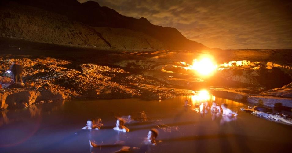 14.dez.2012 - Israelenses se banham em águas termais na costa do mar Morto, próximo ao Kibutz de Ein Gedi, enquanto observam o céu à espera da uma chuva de meteoro de Gêmeos, que deve ocorrer na madrugada desta sexta-feira (14). Acredita-se que o evento, que acontece todo ano em dezembro, seja causado pela passagem do asteroide 3200 Phaethon e tem o nome por acontecer na direção da constelação de gêmeos