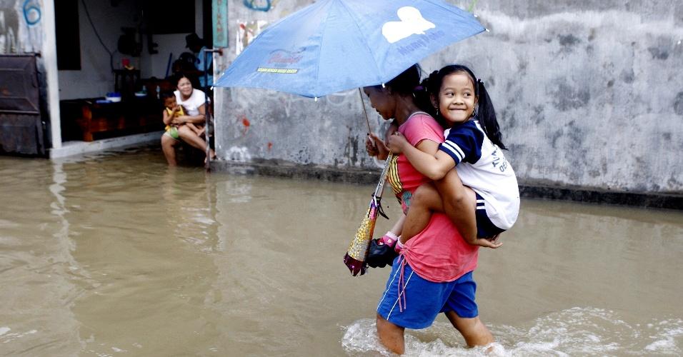 14.dez.2012 - Mulher carrega a filha em rua alagada em área residencial da cidade de Denpasar, em Bali, Indonésia, nesta sexta-feira (14)
