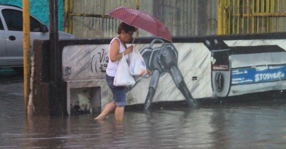 14.dez.2012 - Mulher passa por ponto de alagamento na avenida Água Fria, zona norte de São Paulo (SP), nesta sexta-feira (14), depois que forte chuva atingiu a cidade