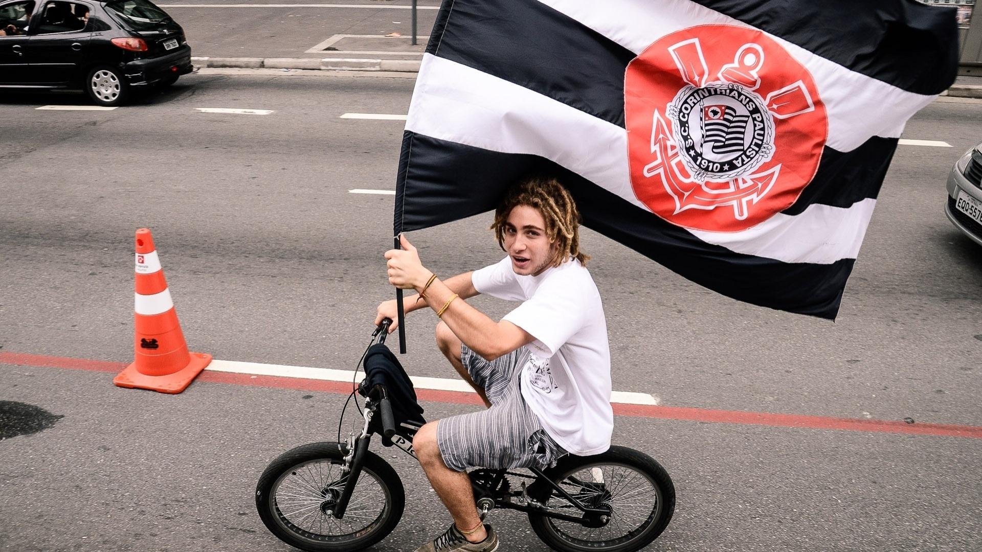 16.dez.2012 - Corintiano anda de bicicleta na ciclovia da Avenida Paulista e carrega bandeira do clube em comemoração do título