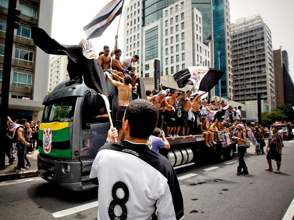 16.dez.2012 - Corintianos 'invadem' caminhão na Avenida Paulista e comemoram conquista do Mundial